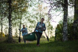 Kuvassa kaksi naista kantaa kanoottia (kuvituskuva).