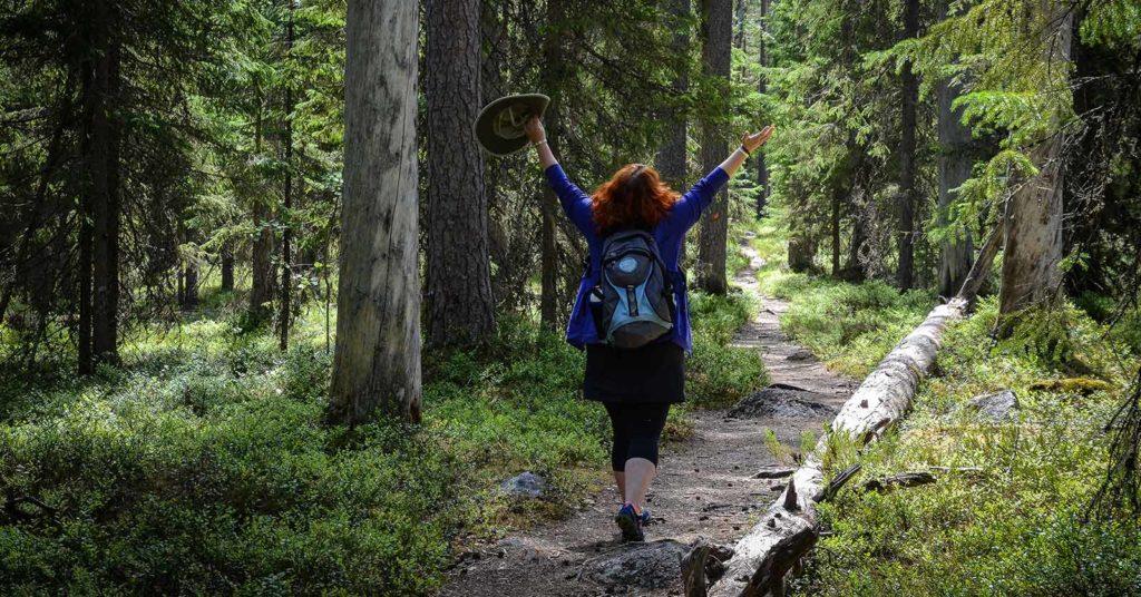 Iloinen retkeilijä nauttii luonnosta Pyhä-Häkin kansallispuiston polulla